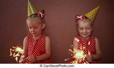 Two charming little sisters twins in holiday caps with sparkling Bengal lights in their hands having fun on a holiday.