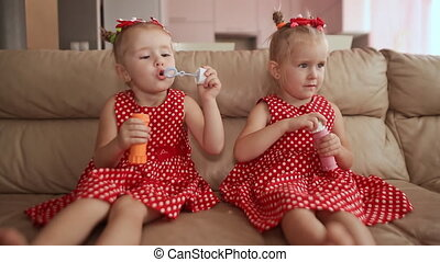 Two little twin sisters in charming red dresses are blowing soap bubbles cheerfully while sitting in the room barefoot.