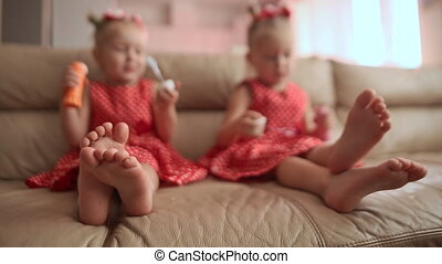 Two little twin sisters in charming red dresses are blowing soap bubbles cheerfully while sitting in the room barefoot. View with emphasis on legs.