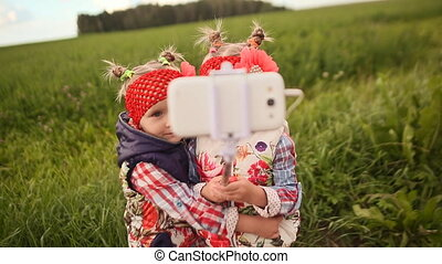 Two cute little twin sisters photograph themselves on a green meadow, using a phone and a stick for selfie.