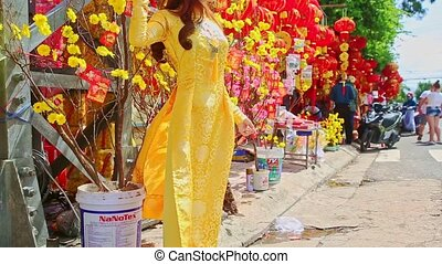 Young Girl Poses by Flowers on Street Market New Year TET