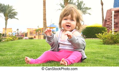 Happy cute baby in park clapping her hands in slow motion