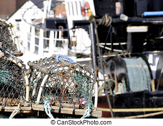Fishing industry - Close up of lobster baskets with trawler...