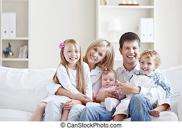 Joyful family - A happy young couple on the couch at home