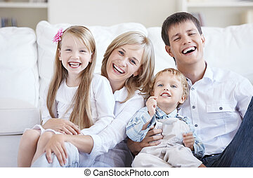 Sweet home - Smiling young parents with two children at home