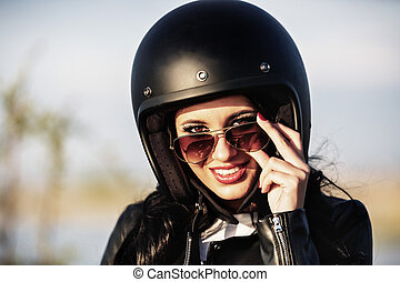Beautiful motorcycle brunette woman with a classic...