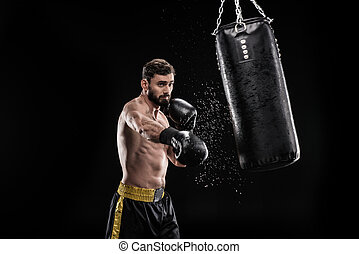 Boxer with punching bag - Young muscular boxer exercising...