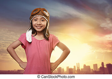 Funny asian kid with aviator hat dreaming of becoming a...