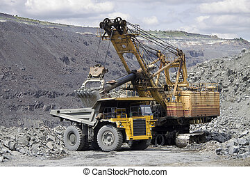 Opencast - Heavy mining dump truck being loaded with iron...