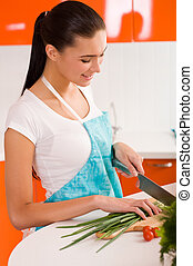 Young woman cutting vegetables in a kitchen