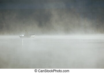 fishing in the fog - fishing in early morning mist over a...