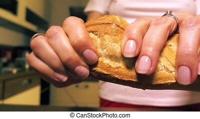 Young woman breaking fresh french bread. Close-up slow...