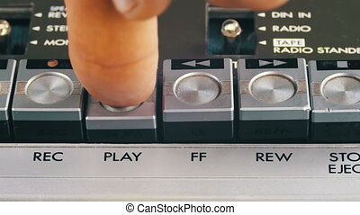 Finger Presses Play and Stop Control Buttons on Audio...