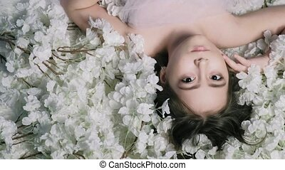 Beautiful girl lies on flowers and smiles, indoors