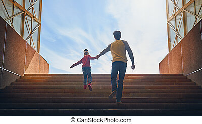 Father and child climb upstairs. Cute girl pulls her dad...
