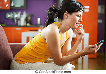 nervous woman holding cellphone - mid adult woman on sofa...