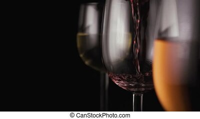 Red wine is poured into one of the three glasses