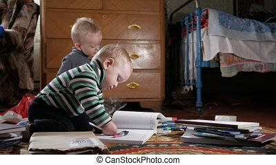 Two boys play at home with stationery. Cute brothers spend...