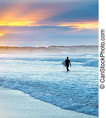 Surfer at sunset - Surfer with surfboard in the ocean at...