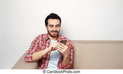 Young man with smartphone at home - Happy smiling young man...