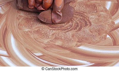 Drawing on a potter whee - Potter paints clay on a potter's...