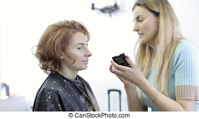 Artist applying blusher to a model before shooting