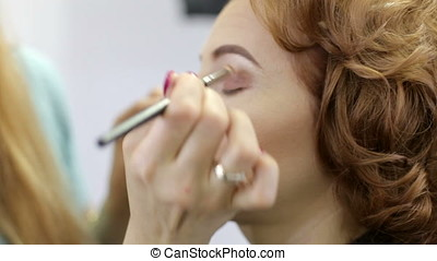 Make-up artist applying blusher to a model before shooting