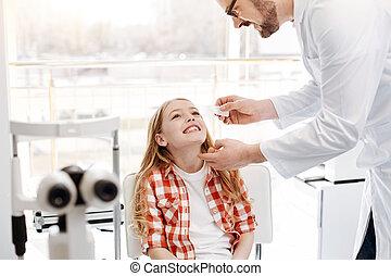 Careful prominent doctor instilling eyedrops - Professional...