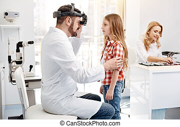 Qualified prominent doctor doing a checkup on girls eyes