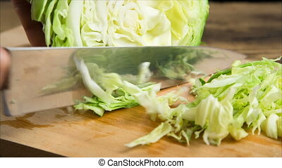Slicing cabbage on wooden cutting board - Slicing cabbage...
