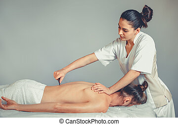 Massage gua, sha therapy. A young professional female...