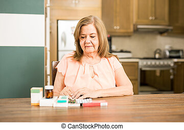 Senior mature woman looking at her medicines - Old Latin...