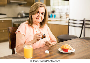 Retired woman taking some pills in the morning - Healthy old...
