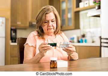 Elderly woman checking her medicines expiration date - Good...