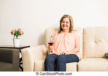 Mature woman drinking wine - Joyful good looking woman...