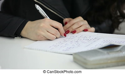 Woman taking notes in the class. Writing in a notebook
