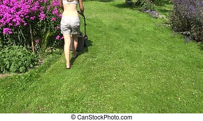 Young female in yard pushing grass trimming lawnmower. 4K -...