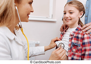 Portrait of smiling little patient looking at her doctor -...