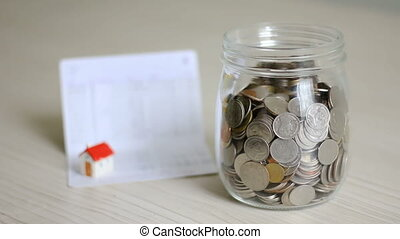 Money coin falling into glass jar and blur house and book...
