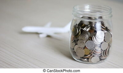 Money coin falling into glass jar and blur air plane behind...
