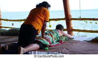 girl doing massage to guy outdoors.