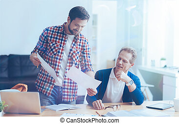Smiling male colleagues working together in the office