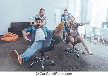 Positive colleagues riding in office chairs - Go ahead....