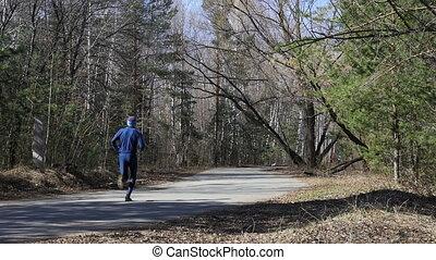 athletic runner man running asphalt road in city park