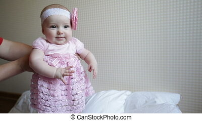 Mom learns to walk a little baby girl in a pink dress