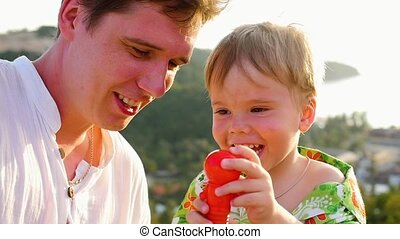 The guy with the child is playing fun, laughing. Close-up