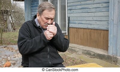 An elderly man with a mustache smokes in the street near the old house. Dressed in a black sweater
