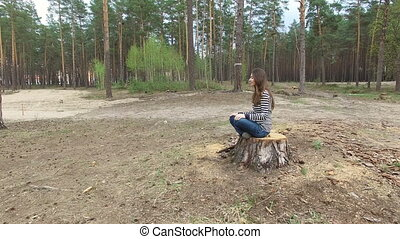 Beautiful young woman sits on a stump in a summer pine park.