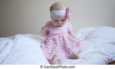 Little baby girl in pink dress is sitting on the bed in the bedroom