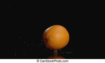Slo-motion orange falling on dark background with copy space